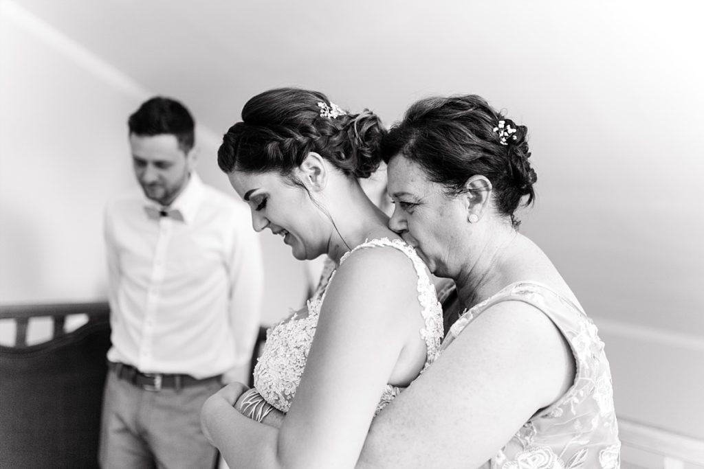 Pendant les préparatifs du mariage, la maman sert dans ses bras sa fille en tenue de mariée qui est de dos.