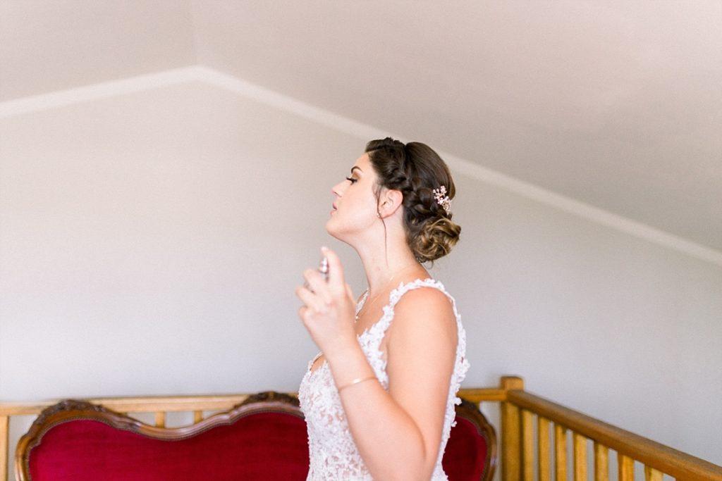 La mariée mets son parfum pendant ses préparatifs de mariage à côté de Manosque