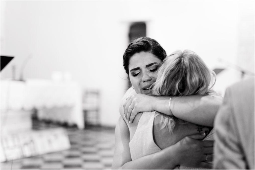 La mariée pleure d'émotion en serrant dans ses bras sa tante dans l'église