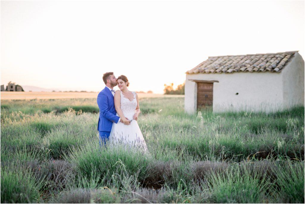 Le marié embrasse le front de sa femme lors de la séance photo couple mariage à Valensole