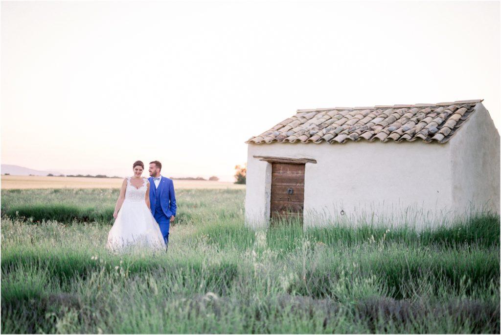 Seance photo de couple lors du mariage de Lara et Joao dans un champs de lavande. Les mariés marchent à côté d'un cabanon provencal