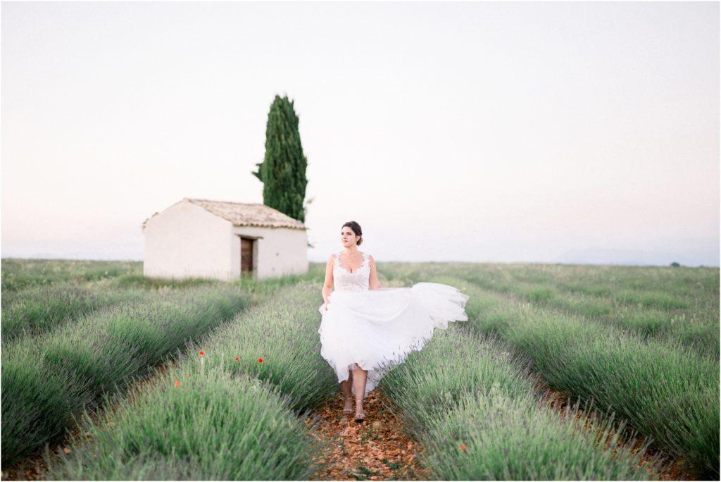 La mariée fait bouger sa robe lors de sa seance couple de mariage à Valensole