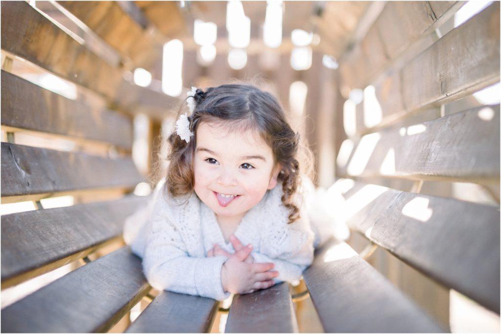 Petite fille qui tire la langue allongée dans un jeu de parc lors d'une séance photo famille entre Pertuis et Manosque