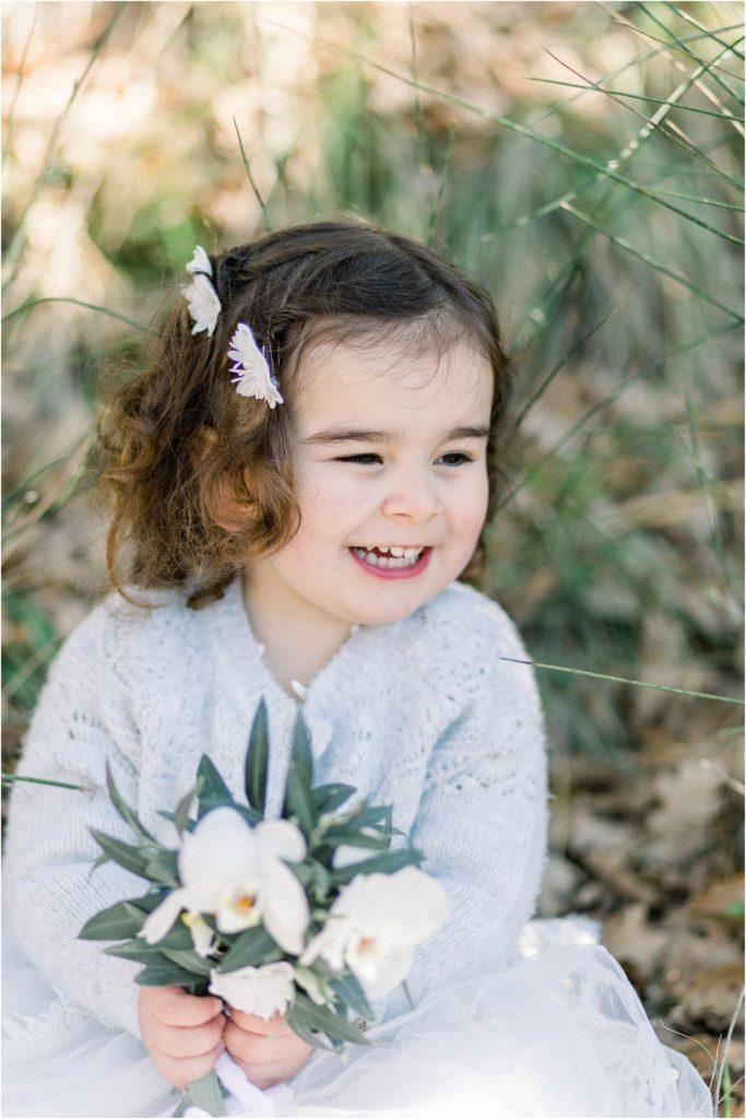 Seance photo famille entre Pertuis et Manosque où la petite fille tient un bouquet de fleurs et sourit.