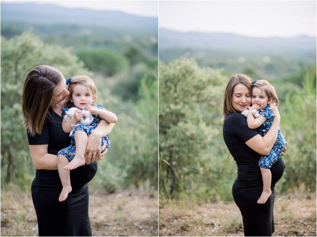 Seance photo grossesse en famille dans la nature, une maman porte sa fille de 18 mois dans les bras