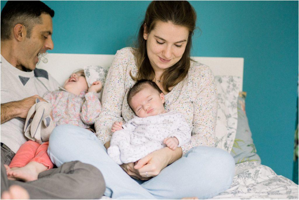 Séance bébé nouveau né endormi avec complicité des parents et la grande soeur