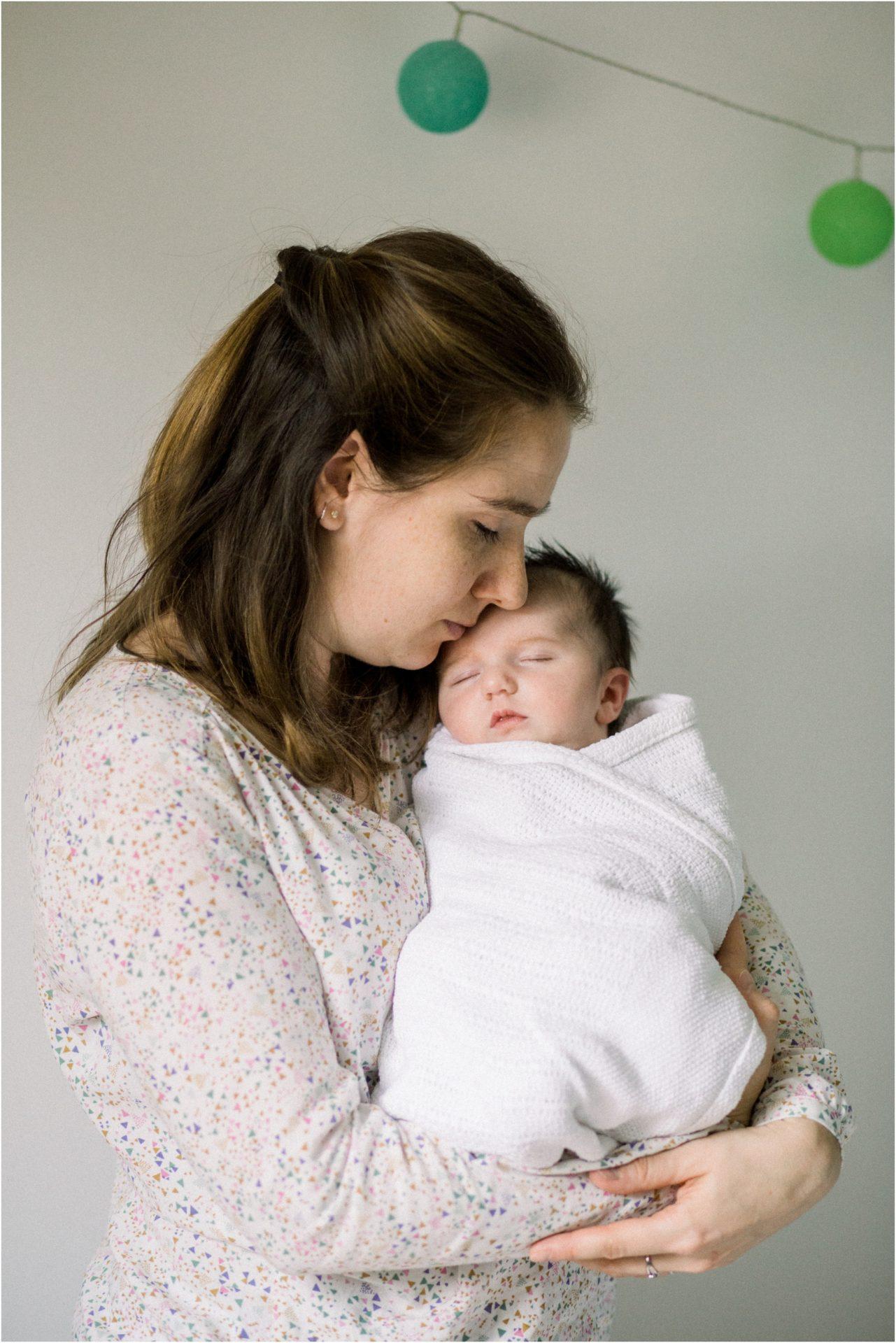 Shooting nouveau né avec maman qui prend son bébé dans les bras